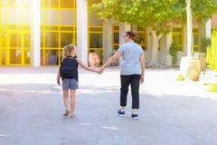 Bambina con la borsa di scuola o cartella che cammina alla scuola con la nonna Vista posteriore immagine stock libera da diritti