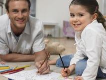 Bambina con la casa di Coloring Book At del padre Immagine Stock