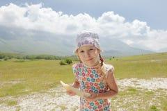 Bambina con la fetta del melone a disposizione che gode essendo sul prato alpino fotografie stock