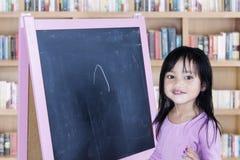 Bambina con la lavagna in biblioteca Fotografia Stock