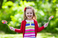 Bambina con la lecca-lecca variopinta della caramella Fotografie Stock