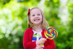Bambina con la lecca-lecca variopinta della caramella Fotografia Stock