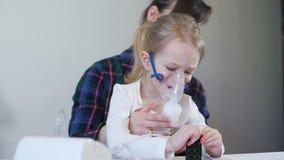 Bambina con la madre che fa inalazione con il nebulizzatore archivi video