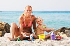 Bambina con la madre sulla spiaggia immagini stock