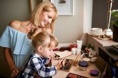 Bambina con la mamma divertendosi con il trucco immagini stock libere da diritti