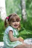 Bambina con la mela in sue mani esterne Fotografia Stock