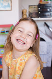 Bambina con la risata gialla del vestito Fotografie Stock