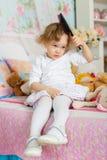 Bambina con la spazzola per i capelli. Fotografie Stock