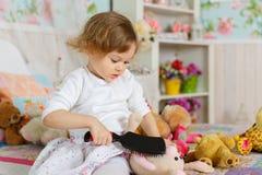 Bambina con la spazzola per i capelli. Immagini Stock