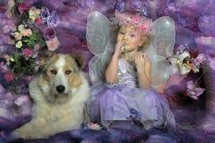 Bambina con le ali e un cane fotografia stock