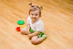 Bambina con le cose del tè del giocattolo Immagine Stock