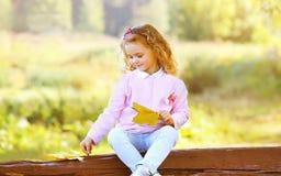 Bambina con le foglie di acero gialle nel parco di autunno Immagine Stock Libera da Diritti