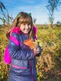Bambina con le foglie di autunno e lo Zaino rosa che cammina allo scho fotografia stock libera da diritti