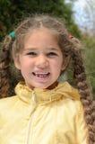 Bambina con le trecce lunghe e la mancanza del dente all'aperto in immagini stock libere da diritti