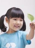 Bambina con le trecce nel riciclaggio della maglietta di simbolo che esamina foglia, fine sul colpo dello studio Fotografia Stock Libera da Diritti