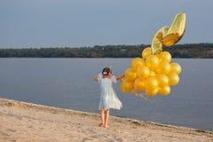 Bambina con molti palloni dorati sulla spiaggia al tramonto Immagine Stock Libera da Diritti