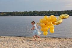 Bambina con molti palloni dorati sulla spiaggia al tramonto Immagini Stock Libere da Diritti