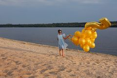 Bambina con molti palloni dorati sulla spiaggia al tramonto Immagine Stock