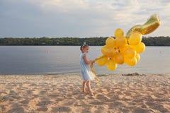Bambina con molti palloni dorati sulla spiaggia al tramonto Immagini Stock