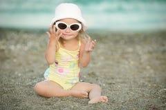 Bambina con sindrome di Down che gioca gli occhiali da sole sulla spiaggia Immagine Stock