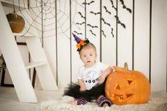 Bambina con sindrome di Down che si siede con una scopa vicino alla grande zucca Fotografia Stock Libera da Diritti