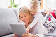 Bambina con sua madre che per mezzo del computer della compressa Immagini Stock Libere da Diritti