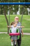 Bambina con suo nonno divertendosi su un'oscillazione in un Gree Fotografia Stock