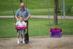 Bambina con suo nonno divertendosi su un'oscillazione in un Gree Fotografie Stock Libere da Diritti
