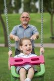 Bambina con suo nonno divertendosi su un'oscillazione in un Gree Fotografie Stock