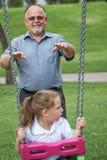 Bambina con suo nonno divertendosi su un'oscillazione in un Gree Fotografia Stock Libera da Diritti