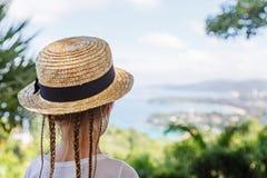 Bambina con un cappello della treccia e di paglia dei capelli che esamina il mare mentre stando sul punto di vista con la bellezz fotografie stock libere da diritti
