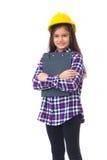 Bambina con un casco e una lavagna per appunti gialli isolati su bianco fotografia stock