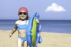 Bambina con un cerchio su una spiaggia sabbiosa del mare Contro lo sfondo del mare e delle nuvole Immagini Stock