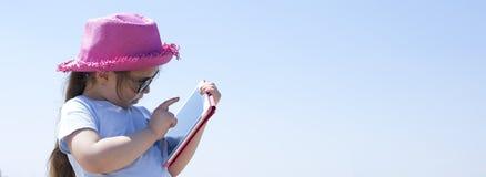 Bambina con un computer della compressa in mani Giorno soleggiato sulla spiaggia e sul cielo blu Copi lo spazio bandiera immagine stock libera da diritti