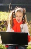 Bambina con un computer portatile immagini stock