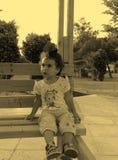 Bambina con un fiore in suoi capelli Immagini Stock