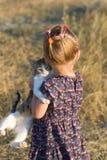 Bambina con un gatto nelle mani Fotografie Stock