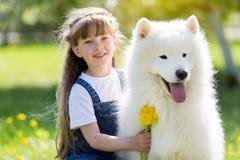 Bambina con un grande cane bianco nel parco fotografia stock