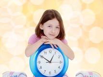Bambina con un grande orologio Fotografia Stock Libera da Diritti