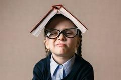 Bambina con un libro sopra la sua testa Fotografia Stock