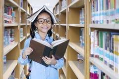 Bambina con un libro sopra la sua testa Fotografie Stock Libere da Diritti