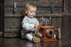 Bambina con un retro telefono immagine stock libera da diritti