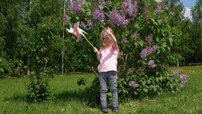 Bambina con una girandola in un parco accanto ad un lillà di fioritura in primavera stock footage