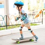 Bambina con una guida del casco sul pattino fotografia stock