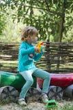 Bambina con una macchina fotografica del giocattolo nel processo creativo Fotografia Stock Libera da Diritti