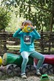 Bambina con una macchina fotografica del giocattolo nel processo creativo Fotografia Stock