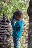 Bambina con una macchina fotografica del giocattolo nel processo creativo Immagine Stock Libera da Diritti
