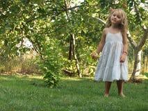 Bambina con una mela in sua mano in mezzo al giardino immagine stock
