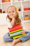 Bambina con una pila di libri Fotografie Stock