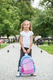 Bambina con uno zaino nel cortile della scuola Il concetto di scuola, studio, istruzione, infanzia immagine stock libera da diritti